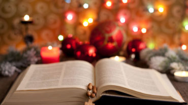 15994954 - christmas and bible with blurred candles light background